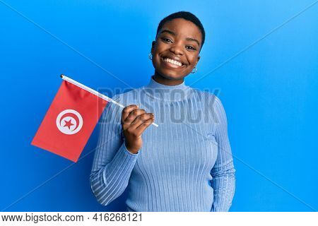 Young african american woman holding tunisia flag looking positive and happy standing and smiling with a confident smile showing teeth