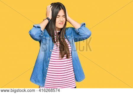 Young brunette woman wearing casual clothes suffering from headache desperate and stressed because pain and migraine. hands on head.