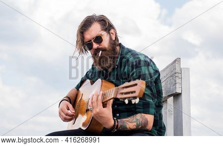 Music Concept. Brutal Handsome Man With Moustache Play Guitar. Mature Musician And Singer. Casual St
