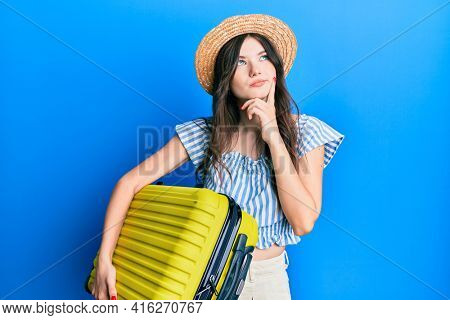 Young beautiful caucasian girl wearing summer dress and holding cabin bag serious face thinking about question with hand on chin, thoughtful about confusing idea