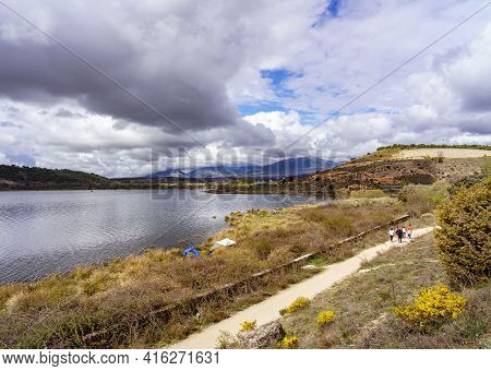 People Strolling Along A Path By The Blue Lake With Reflections In The Water And Storm Clouds. Guada