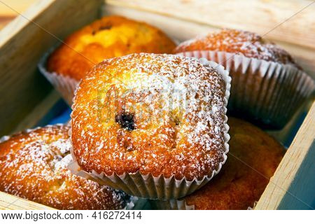 Closeup of mini muffins with icing sugar in wooden box.