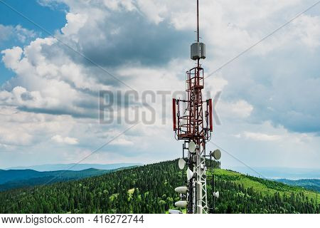 Telecommunication Transmitter Tower With Antennas Of Cellular Communication In Mountains Against Sky