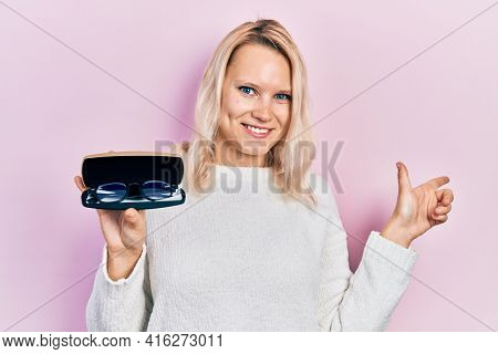 Beautiful caucasian blonde woman holding glasses in eyewear case smiling happy pointing with hand and finger to the side