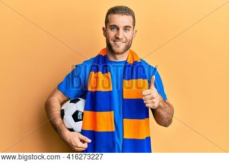 Young caucasian man football hooligan cheering game holding ball smiling happy and positive, thumb up doing excellent and approval sign