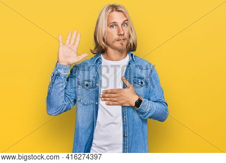 Caucasian man with blond long hair wearing casual denim jacket swearing with hand on chest and open palm, making a loyalty promise oath