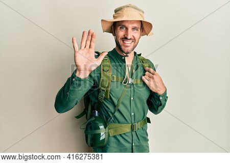 Handsome man with beard wearing explorer hat and backpack waiving saying hello happy and smiling, friendly welcome gesture