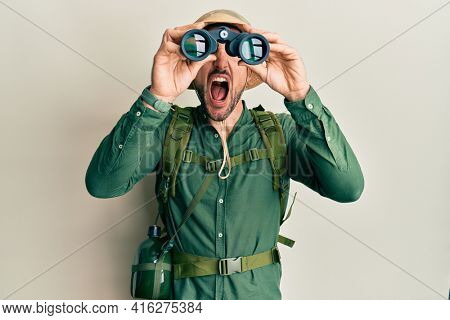 Handsome man with beard wearing explorer hat looking through binoculars angry and mad screaming frustrated and furious, shouting with anger looking up.