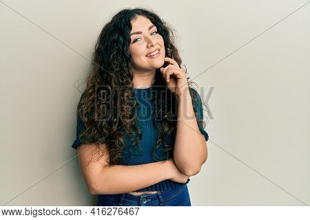 Young brunette woman with curly hair wearing casual clothes looking confident at the camera with smile with crossed arms and hand raised on chin. thinking positive.