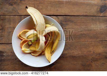 Banana Skin And Orange Peels In White Bowl On Wooden Table Background. Using Banana And Orange Peel