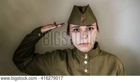 Portrait Of Young Woman In Uniform On Background Of Gray Wall. Female In Soviet Military Uniform Whi