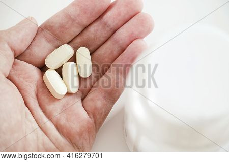 A Man Holding Magnesium Taurate Tablets In His Hand. Close Up.