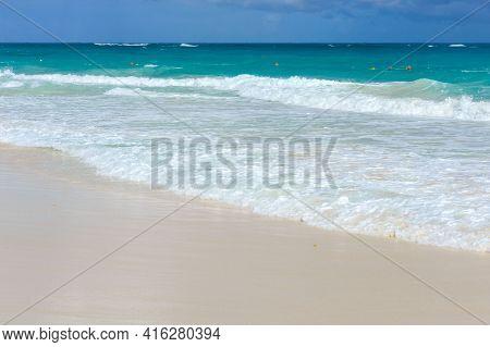A Foamy Wave Runs Over The Sandy Beach. Seascape Turquoise Ocean And Sandy Coast Against The Blue Sk