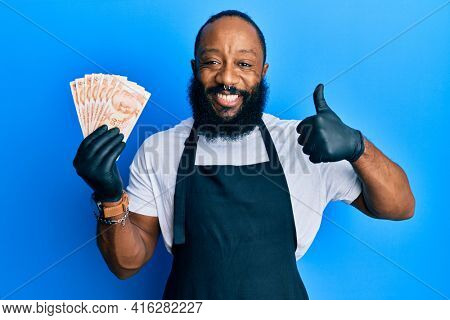 Young african american man wearing professional apron holding turkish liras banknotes smiling happy and positive, thumb up doing excellent and approval sign