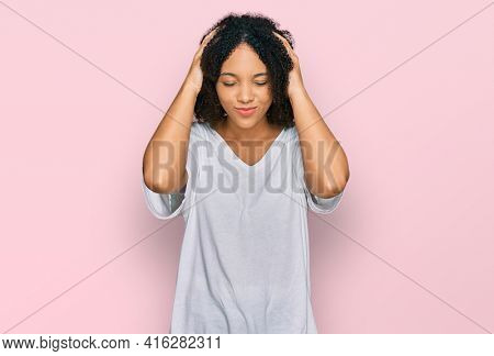 Young african american girl wearing casual clothes suffering from headache desperate and stressed because pain and migraine. hands on head.