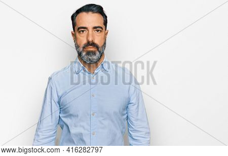 Middle aged man with beard wearing business shirt relaxed with serious expression on face. simple and natural looking at the camera.