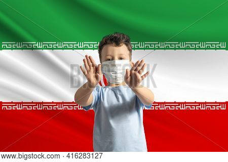 Little White Boy In A Protective Mask On The Background Of The Flag Of Iran Makes A Stop Sign With H
