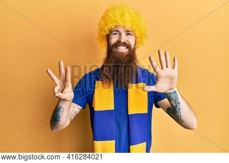 Redhead man with long beard football hooligan cheering game wearing funny wig showing and pointing up with fingers number eight while smiling confident and happy.