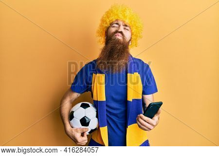 Redhead man with long beard football hooligan cheering game holding smartphone looking at the camera blowing a kiss being lovely and sexy. love expression.