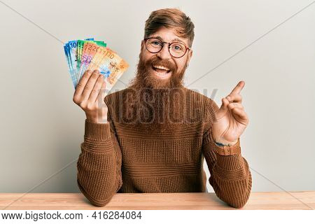Young irish redhead man holding swiss franc banknotes sitting on the table smiling happy pointing with hand and finger to the side