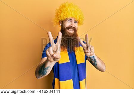 Redhead man with long beard football hooligan cheering game wearing funny wig smiling looking to the camera showing fingers doing victory sign. number two.