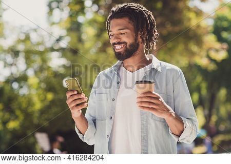 Portrait Of Attractive Handsome Cheerful Guy Using Gadget Chatting Drinking Latte Spending Time On F