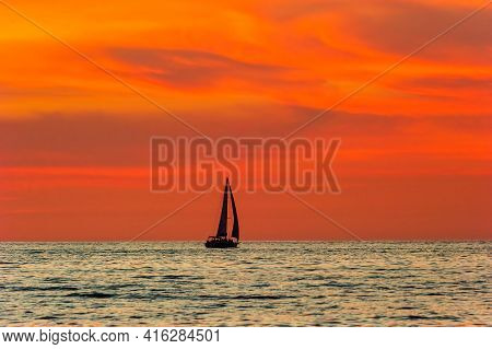 A Sailboat Is Sailing Along The Ocean As A Vivid Colorful Sunset Is In The Background