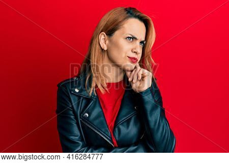 Hispanic young woman wearing black leather jacket thinking concentrated about doubt with finger on chin and looking up wondering