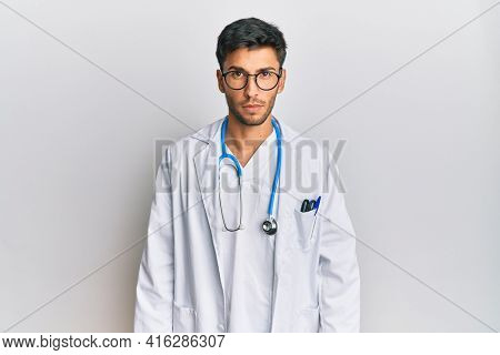 Young handsome man wearing doctor uniform and stethoscope skeptic and nervous, frowning upset because of problem. negative person.