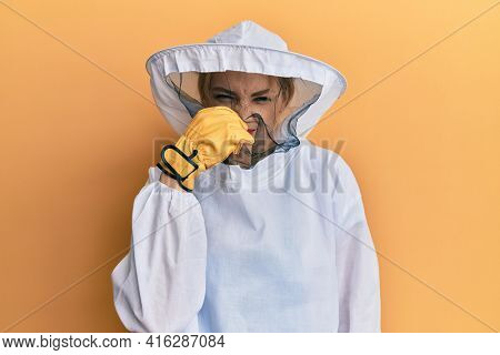 Beautiful blonde caucasian woman wearing protective beekeeper uniform smelling something stinky and disgusting, intolerable smell, holding breath with fingers on nose. bad smell