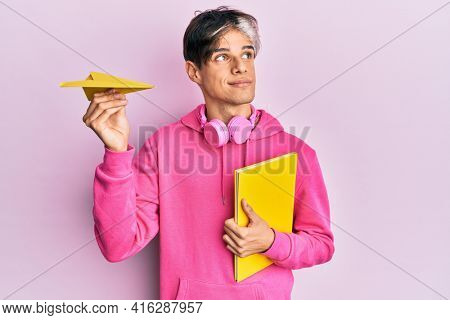 Young hispanic man holding book and paper airplane smiling looking to the side and staring away thinking.