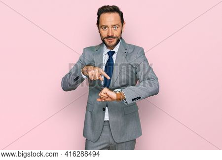 Middle age man wearing business clothes in hurry pointing to watch time, impatience, upset and angry for deadline delay