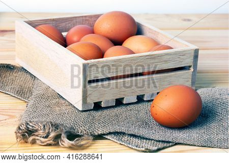 Raw brown eggs in wooden box on canvas fabric on wooden table. Selective focus.