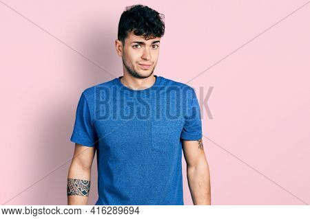 Young hispanic man wearing casual t shirt skeptic and nervous, frowning upset because of problem. negative person.
