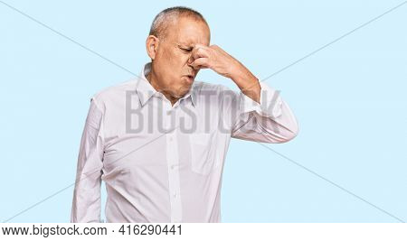 Handsome senior man wearing elegant white shirt smelling something stinky and disgusting, intolerable smell, holding breath with fingers on nose. bad smell