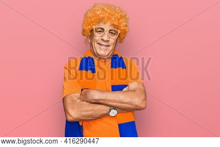 Senior hispanic man football hooligan cheering game happy face smiling with crossed arms looking at the camera. positive person.