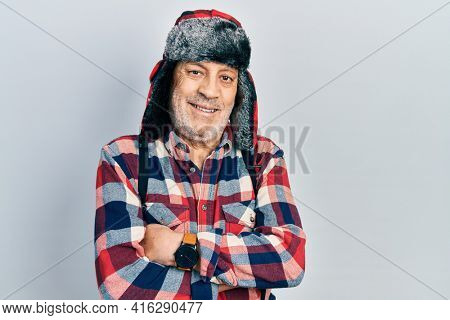 Handsome mature man wearing winter hat with ear flaps happy face smiling with crossed arms looking at the camera. positive person.