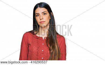 Young hispanic woman wearing casual clothes relaxed with serious expression on face. simple and natural looking at the camera.