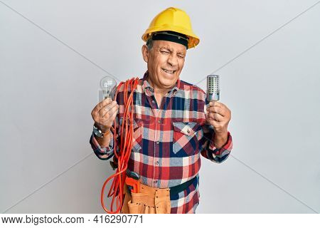Senior hispanic man wearing handyman uniform holding led lightbulb and incandescent bulb winking looking at the camera with sexy expression, cheerful and happy face.