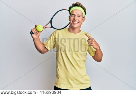 Handsome caucasian man playing tennis holding racket and ball smiling happy pointing with hand and finger