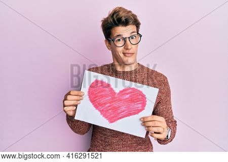 Handsome caucasian man holding heart draw skeptic and nervous, frowning upset because of problem. negative person.