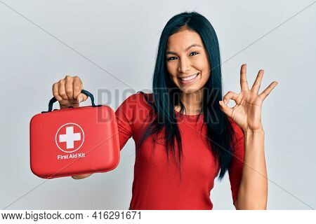 Beautiful hispanic woman holding first aid kit doing ok sign with fingers, smiling friendly gesturing excellent symbol