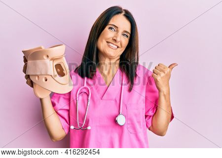 Middle age brunette doctor woman holding cervical neck collar pointing thumb up to the side smiling happy with open mouth