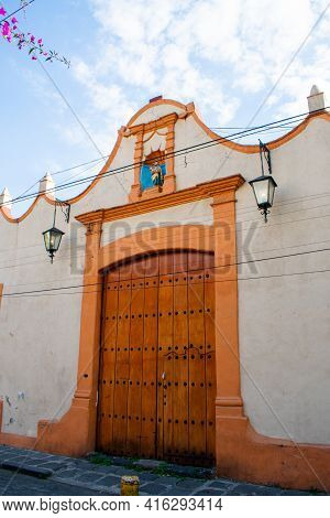 Hispanic Building With Small Religious Altar Above The Tall Door