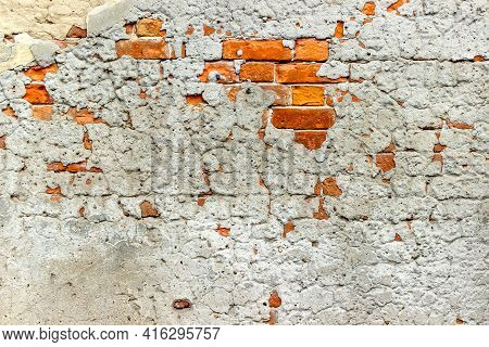 An Old Damaged Brick Wall Partially Covered With Old Cracked Plasterwork As A Background