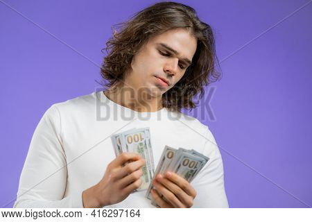 Satisfied Man Counting Usd Currency. Guy With Long Hairstyle Counts Money - Dollars Banknotes On Vio