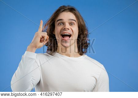 Young Thinking Pondering Man Having Idea Moment Pointing Finger Up On Blue Studio Background. Smilin