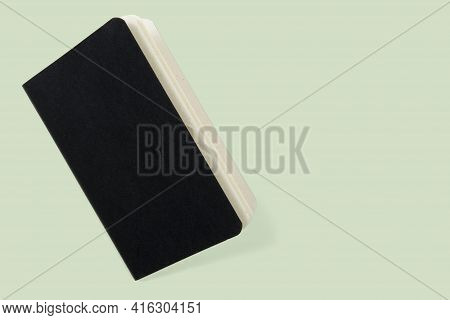 Open Paper Book With Black Cover Isolated On Green Background