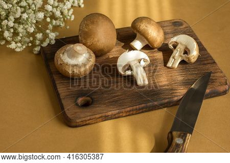 Raw Mushrooms Champignons On A Cutting Wooden Board On A Beige Background In The Rays Of The Sun, Pr