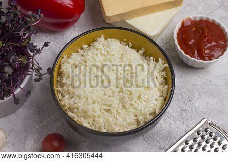 Grated Cauliflower In A Deep Plate. Cauliflower Keto Pizza Dough Making Process.